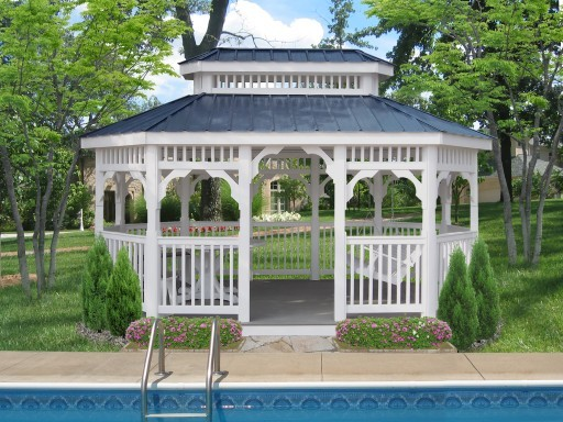 Vinyl oblong Gazebo with picnic table, benches, and swing by a pool